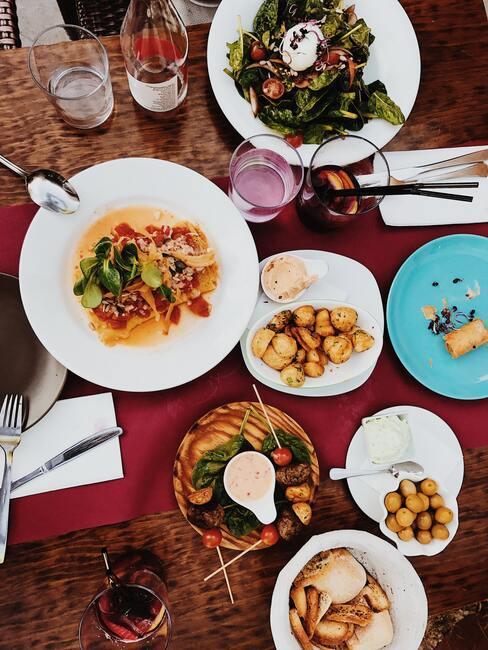 Stół zastawiony przeróżnymi potrawami na białych talerzach na stole z bordowym bieżnikiem