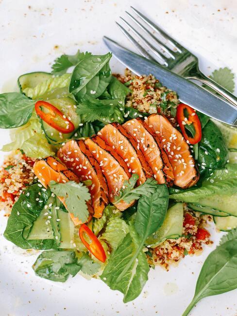 smażone kawałki ryby z sezamem na zielonych jadalnych liściach