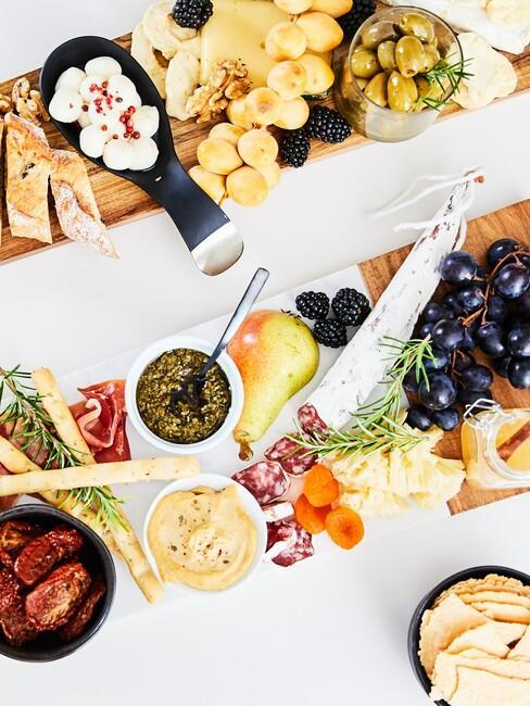 Stół zastawiony przeróżnymi przekąskami i przystawkami takimi jak owoce wędliny, sery czy pasty warzywne