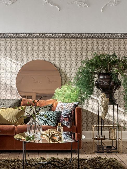 sofa w kolorze rdzy z poduszkami w koloracj jesieni obok wazonu z dużą rośliną