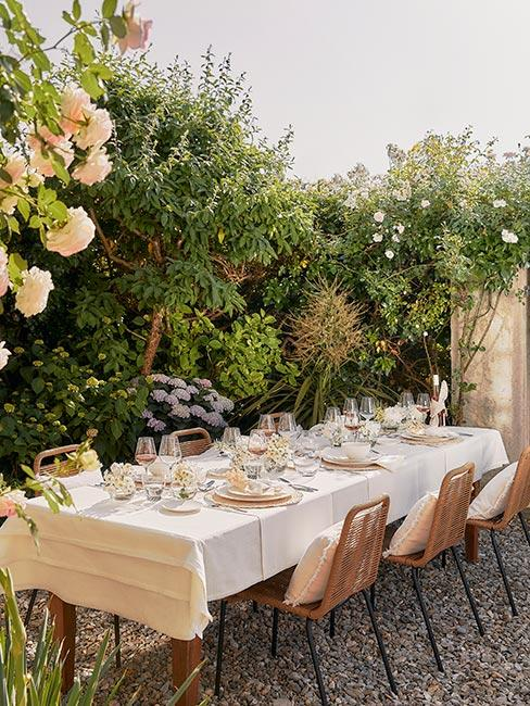 stół nakryty białym obrusem w ogrodzie z białą zastawą i srebrnymi sztućcami