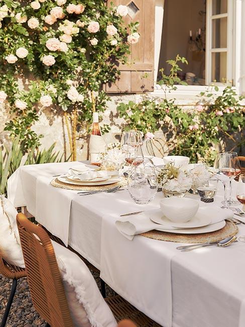 zbliżenie na stół nakryty białym obrusem w ogrodzie z białą zastawą i srebrnymi sztućcami