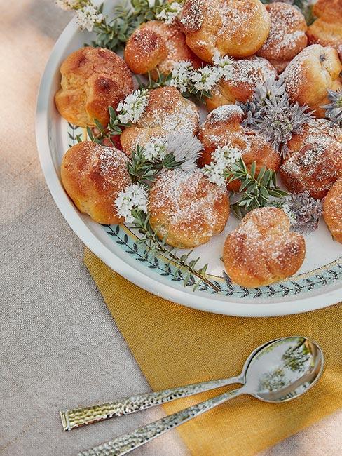 małe pączki z cukrem pudrem w białozielonej misce