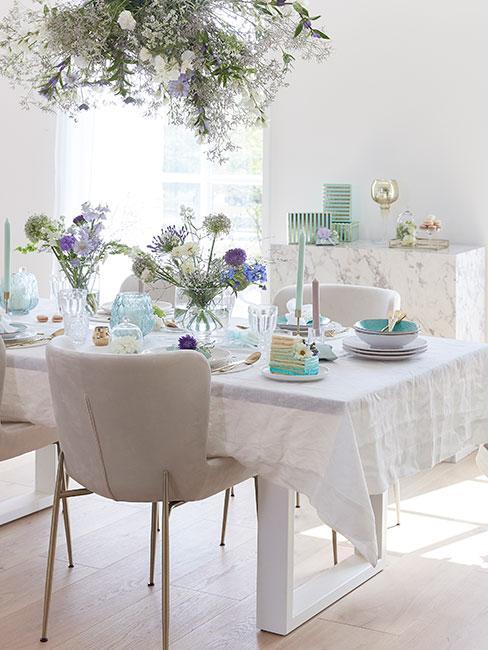 stoł nakryty białym obrusem z seledynowymi dekoracjami i zastawą
