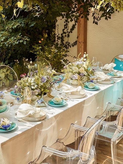 stoł w ogrodzie nakryty białym obrusem z seledynowymi dekoracjami i zastawą