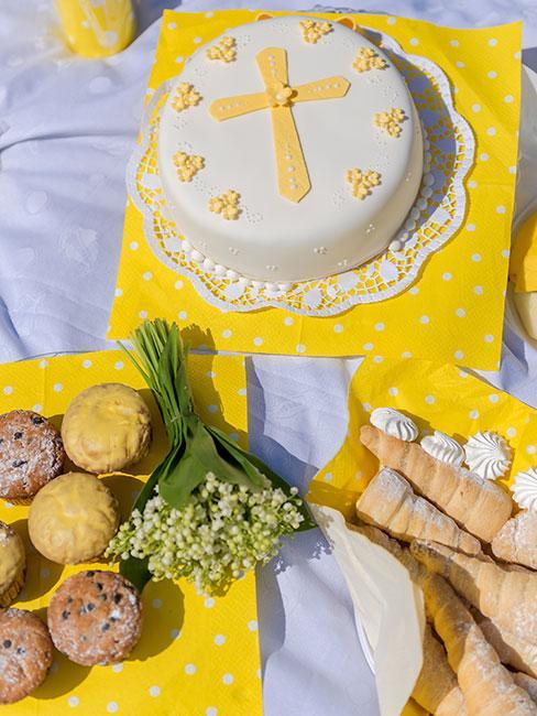 jasnożółty tort na chrzest na żółtmy obrusie obok pączków i bukiecika konwalii