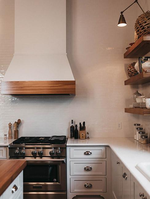Kuchnia w stylu farmhouse, białe szafki wraz z blatem, ozdobne uchwyty okap biały z drewnianą odwódką