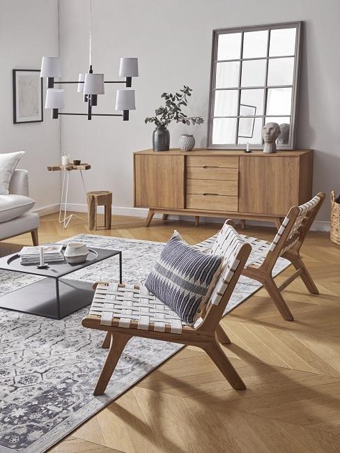 Salon z drewnianą podłogą, szarą ścianą, jasnym dywanem drewnianymi meblami i dodatkami w jasnych odcieniach