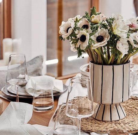 farmhouse: beżowy wazon w czarne paski, na podkładce z juty, w nim białe kwiaty, obok zastawa stołowa w jasnych kolorach