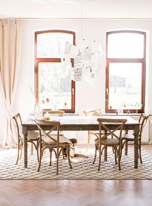 Przestronna jadalnia z drewnianym stołem i krzesłami na których leżą poduszki w jasnych barwach, podłoga przykryta dywanem, jasne zasłony i duże drewniane okna