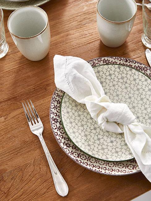 farmhouse: wzorzysta bezowa zastawa stołowa, białą dekoracyjną serwetką na drewnianym stole