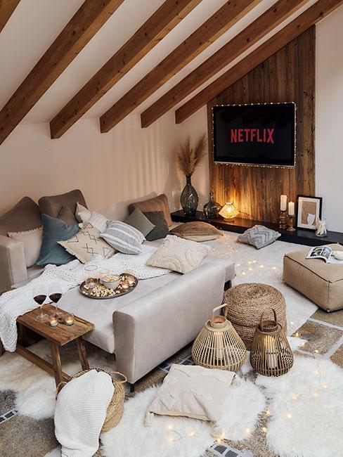 Przestronna sypialnia na poddaszu z kominkiem w rogu, mnóstwem dekoracyjnych poduszek w jasnych barwach, oraz łóżkiem w szarym odcieniu