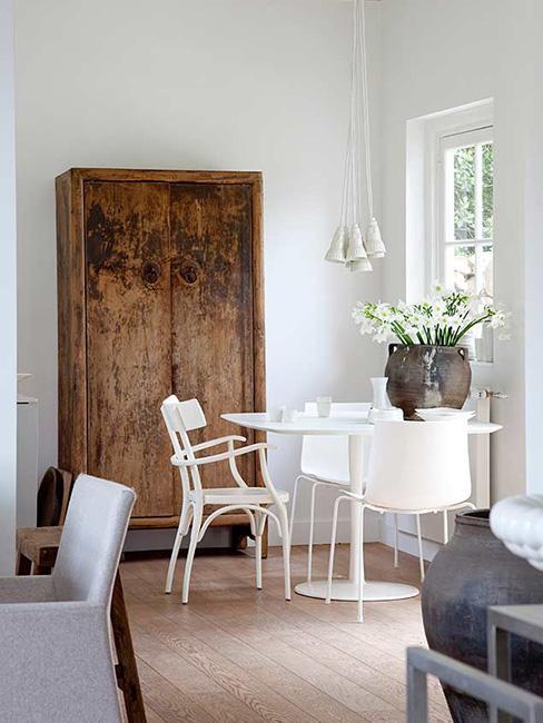 zabytkowa szafa w części jadalnianej obok biały stół z krzesłami i wazon z kwiatami