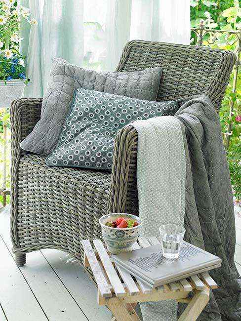 Wiklinowy fotel na tarasie z ozdobnymi błękitnymi poduszkami i pledem w kolorze białym i szarym