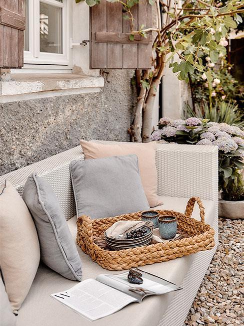 Sofa na zewnątrz w jaksnym kolorze, z dekoracyjnymi poduszkami, i wiklinową tacą