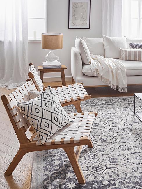 salon w stylu farmhouse, szary wzorzysty dywan na drewnianej podłodze i dwa plecione krzesła z dekoracyjnymi poduszkami