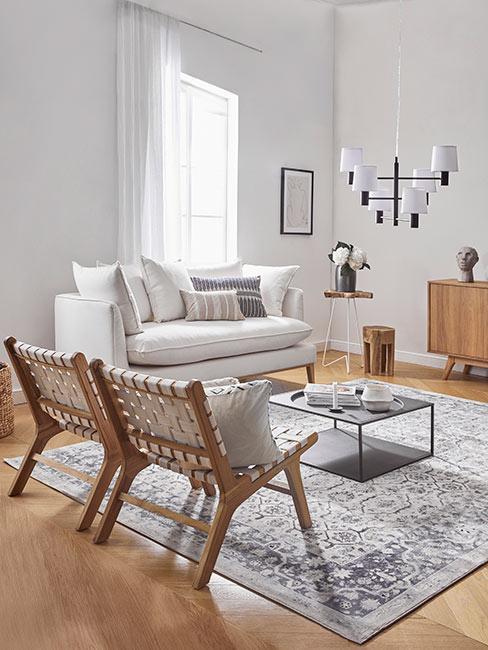 Salon w jasnych barwach, drewniana podłoga, dywan w jasnym kolorze, dwa plecione krzesła z dekoracyjnymi poduszkami, duża biała sofa pod oknem i mały kawowy stolik na środku pomieszczenia