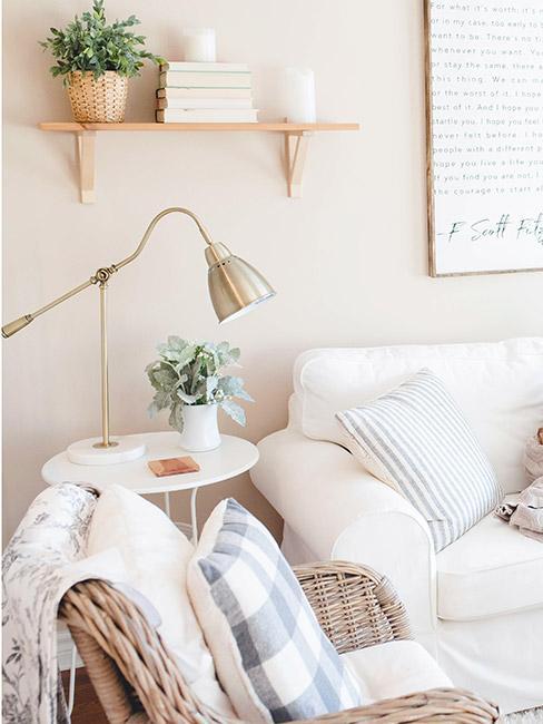 farmhouse: Sofa w jasnym odcieniu, z dekoracyjnymi poduszkami w pastelowych kolorach, wiklinowe wykończenie mebli, drewniana półka z dekoracjami na ścianie