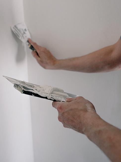 dłonie mężczyzny tynkujące ścianę