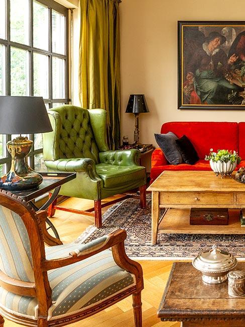 drewniany stolik na środku pokoju, fotel z zielonym kolorze, czerwona sofa,