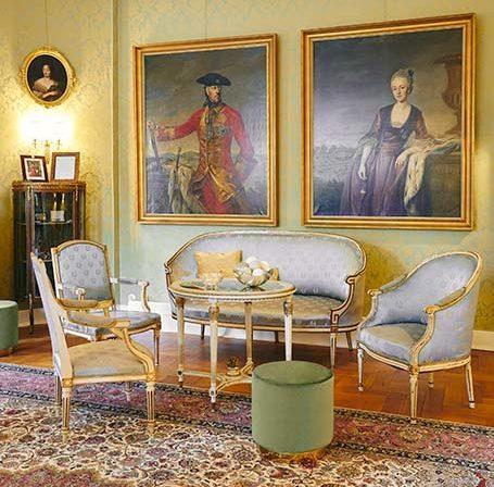 Salon z wzorzystym dywanem, zestawem mebli ze złotym rantem i błękitnym obiciem i dwoma obrazami na ścianie w złotych ramach