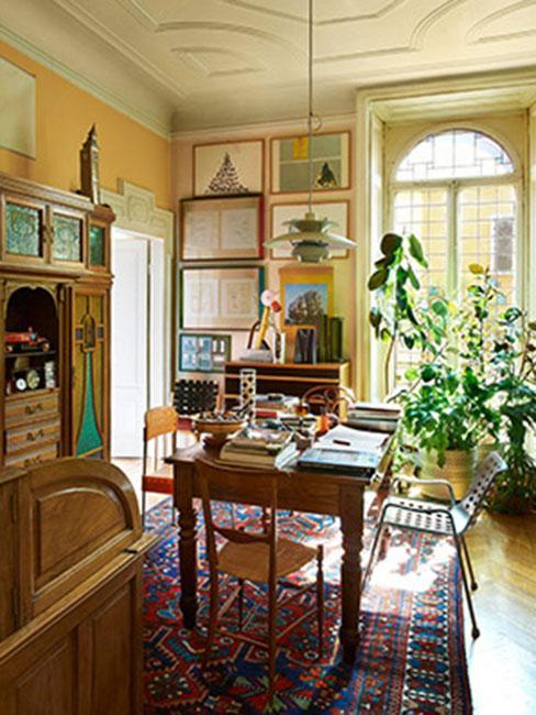Bogato zdobione wnętrze w stylu biedermeier obrazki na zółtej ścianie, rośliny w różnych częsciach pomieszczenia, drewniany stół zastawiony rzeczami, pod ścianą szafka z jasnego drewna