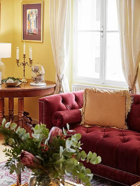 biedermeier: sofa w kolorze bordowym, z poduszką dekoracyjną w kolorze jasnej pomarańczy, obok drewniany tolik, na ścianie zółta farba