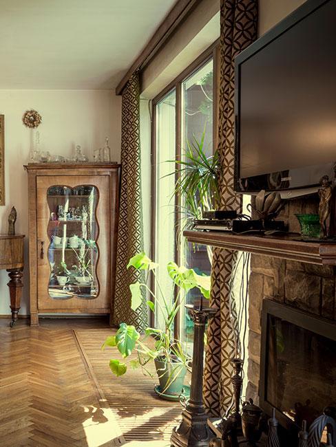 drewniana podłoga, duże przeszklone drzwi, zasłony w ciemnym wzorzystym kolorze, w tle ała witryna z jasnego drewna
