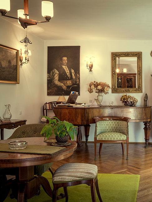 biedermeier: drewniana podłoga, meble z ciemnego drewna, obicie krzesła w jasnozielonym kolorze, na ścianach obrazy i lustra w ozdobnych złotych ramach