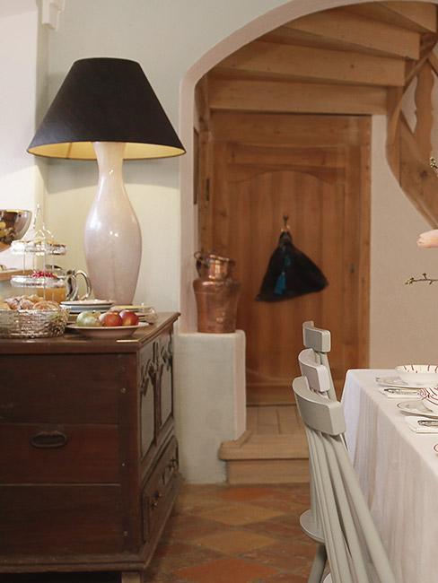 Jadalnia w stylu biedermeier, białe krzesła i stół przykryty białym obrusem, komoda z ciemnego drewna a na niej duża biała lampa z czarnym kloszem