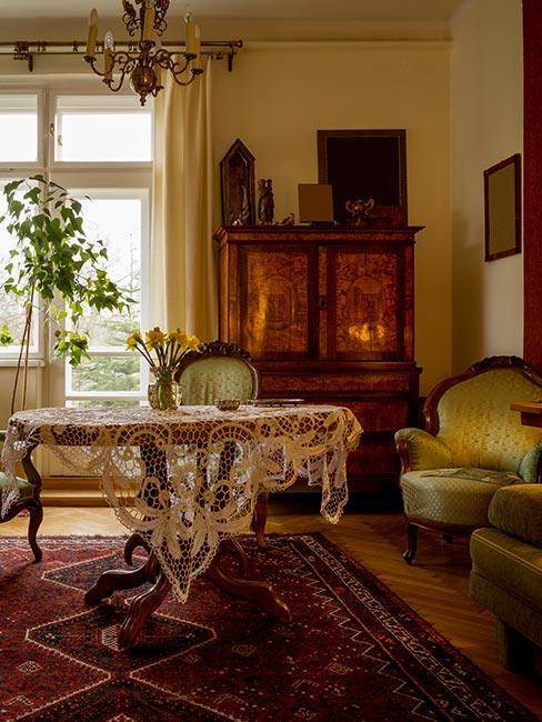 Salon z wzorzystym dywanem w kolorze czerwonym na nim stolik przykryty ażurowym obrusem, obok siedziska z drewnianym rantem i jasnozielonym obiciem, w tle zabytkowa szafa z ciemnego drewna