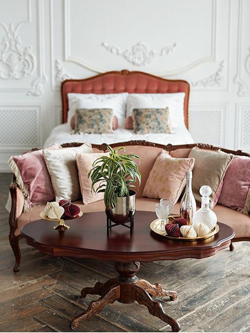 Biedermeier: sypialnia ze zdobieniami na białej ścianie, zagłówek łóżka w ciepłym kolorze, biała pościel z dekoracyjnymi wzorzystymi poduszkami, przed łózkiem mała sofa w kolorze bladego różu z mnóstwem dekoracyjnych poduszek, przed sofą stolik kawowy z ciemnego drewna
