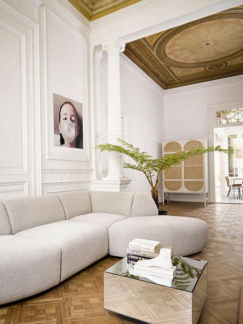nowoczesny salon z szarą sofą modułową w kamienicy z lamperią na ścianie