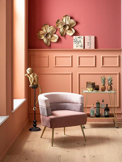 dwukolorowy salon w odcieniach brzoskwini i maliny z lamperią przy dwukolorowym fotelu i złotą lampą w kształcie małpy