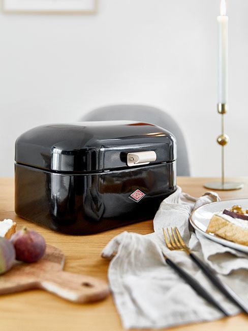 czarny pojemnik na chleb na drewnianym stole