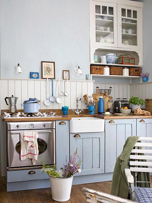 rustykalna kuchnia z błękitnymi szafkami i drewnianym blatem