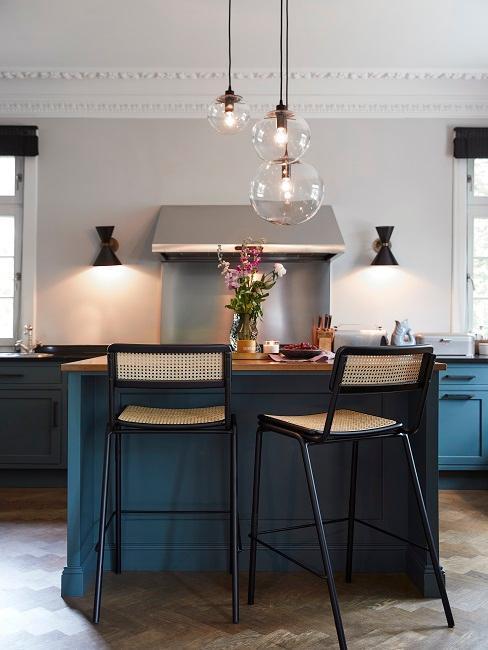 nowoczesna kuchnia z wyspa i szafkami w kolorze morskim przy czarnych krzesłach barowych z plecionką wiedeńską