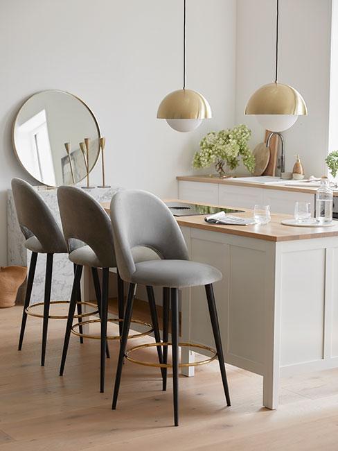 biała kuchnia w wyspą z drewnianym blatem przy szarych krzesłach barowych z aksamitu pod złotymi wiszącymi lampami