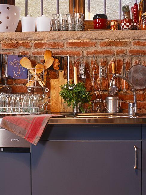 niebieska kuchnia z ceglaną ścianą