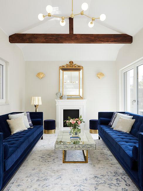 Salon z sofami w kolorze granatowym , złote dodatki, białe ściany i drewniana belka na suficie