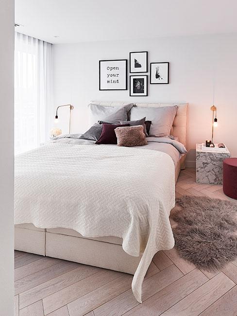 Sypialnia w jasnych kolorach, biały pled na łózku, poduszki dekoracyjne w kolorach różu, beżu i szarości