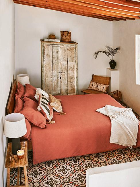 mała orientalna sypialnia z orietnalną wykładziną, szafą z surowego drewna i pościelą w kolorze terakoty