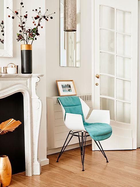 turkusowe nowoczesne krzesło przy kominku w kamienicy