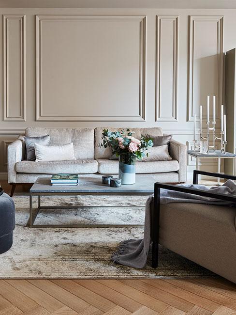salon w kamienicy z lamperią na ścianie z popielatą sofą