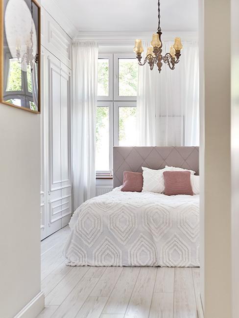 sypialnia z tapicerowanym łóżkiem w pudrowym różu i złotym żyrandolem