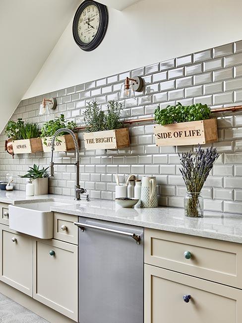 kuchnia na poddaszu w stylu farmhouse z szarymi kafelkami i pojemnikami na zioła z angielskimi napisami