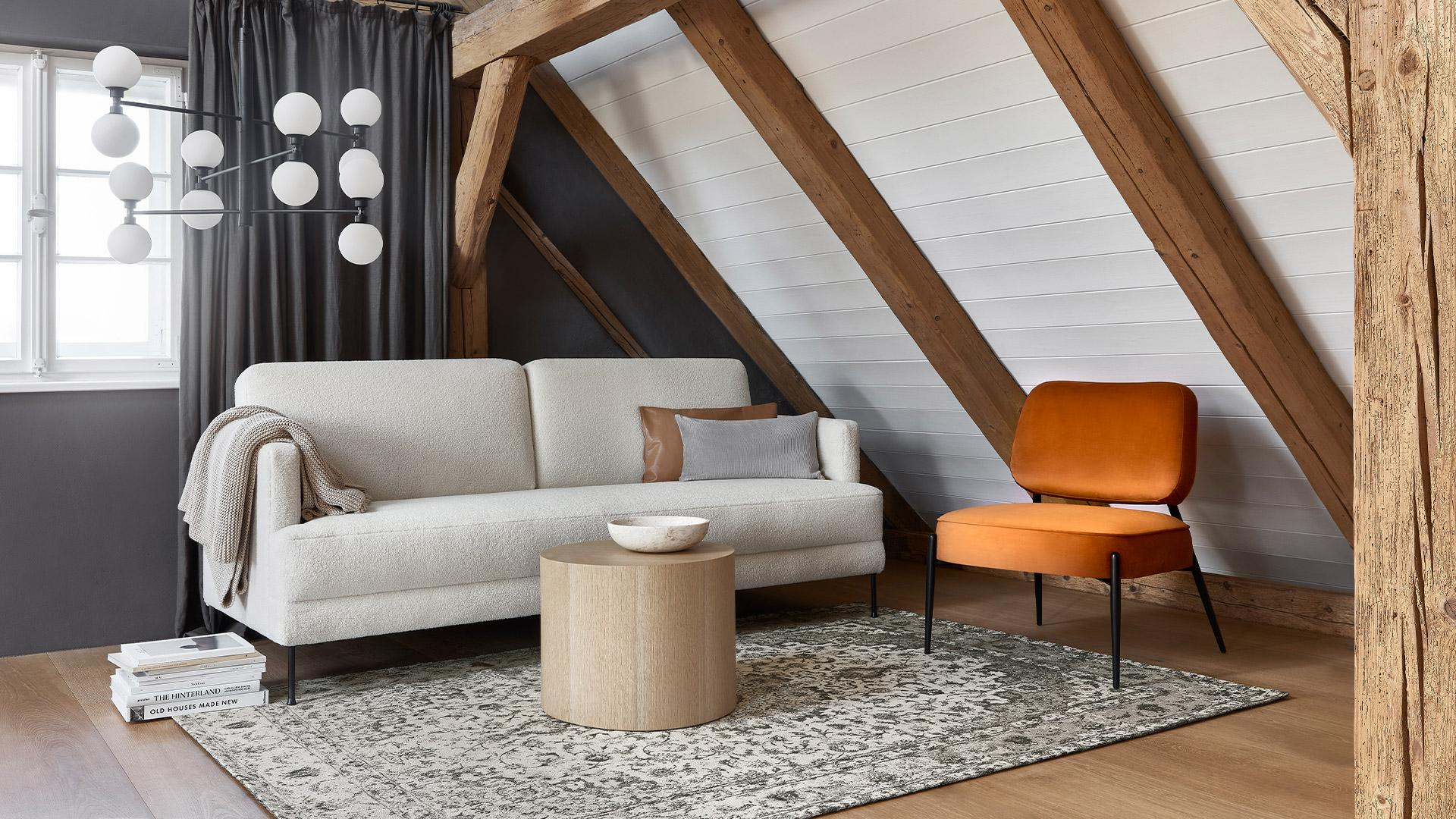 beżowa sofa na poddaszu w lofcie przy pomarańczowym krześle z aksamitu