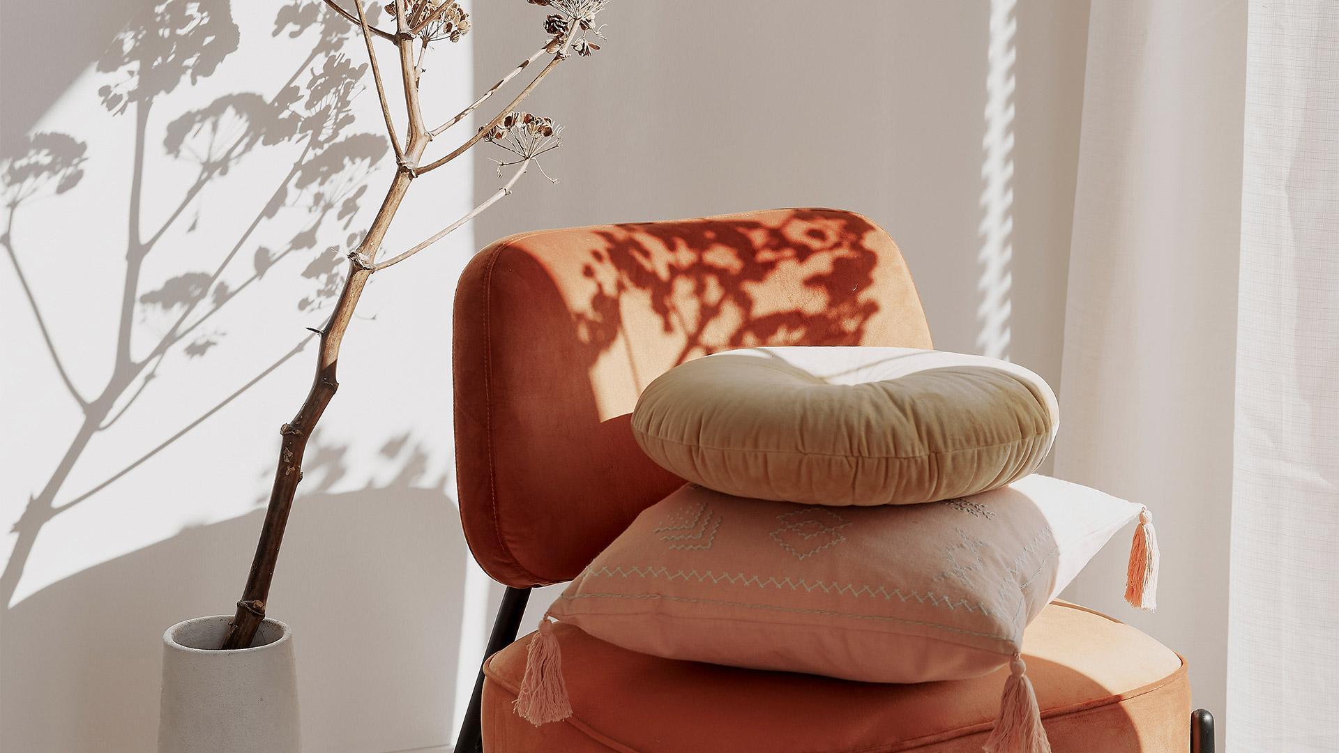 pomarańczowe krzesło z beżowymi poduszkami