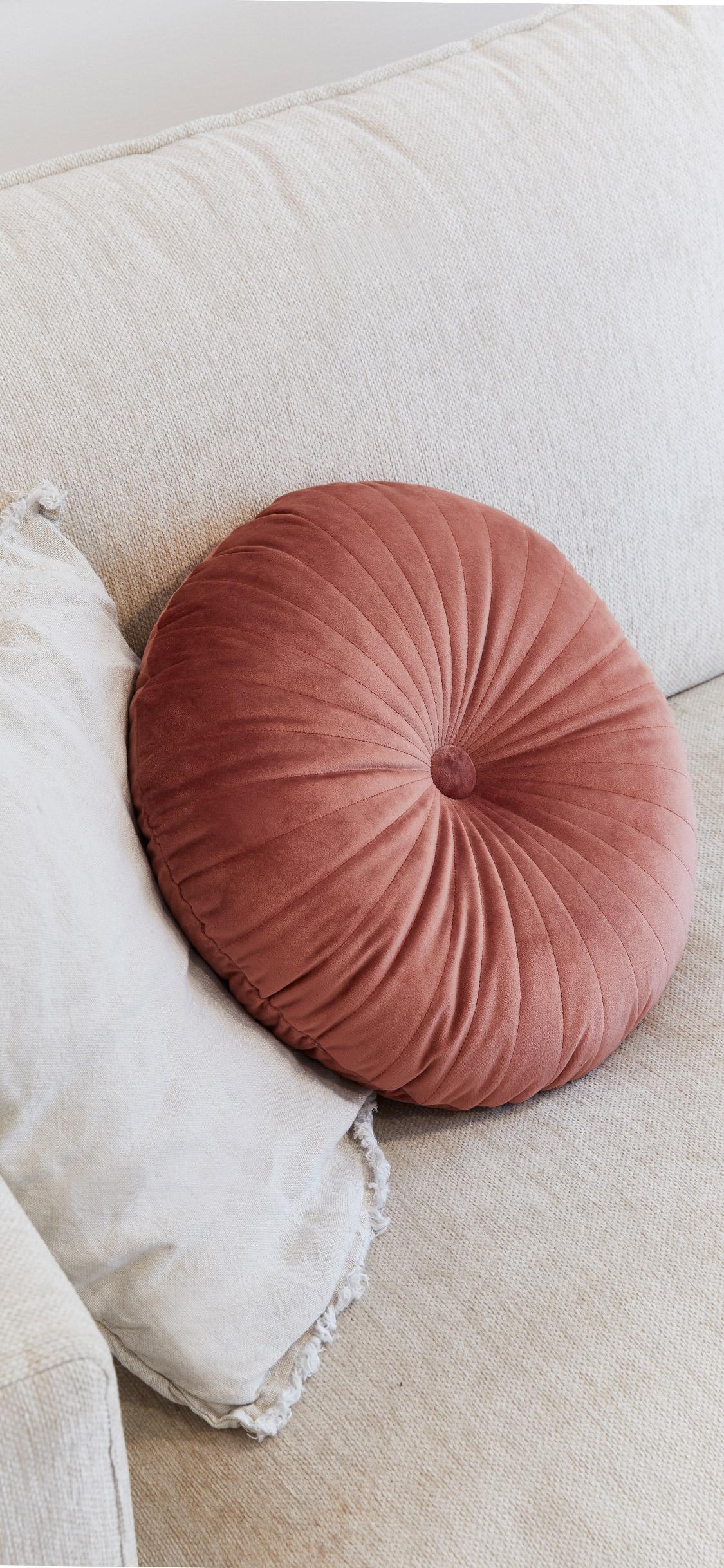okrągła różowa poduszka z aksamitu na beżowej sofie