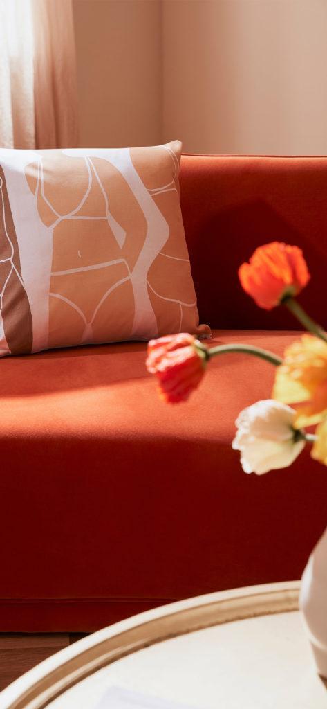 zbliżenie na pomarańczową sofę z tulipanami na pierwszym planie